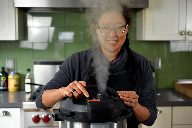 A dark haired smiling woman is manually releasing the pressure on an Instant Pot and the steam is right in front of her face.