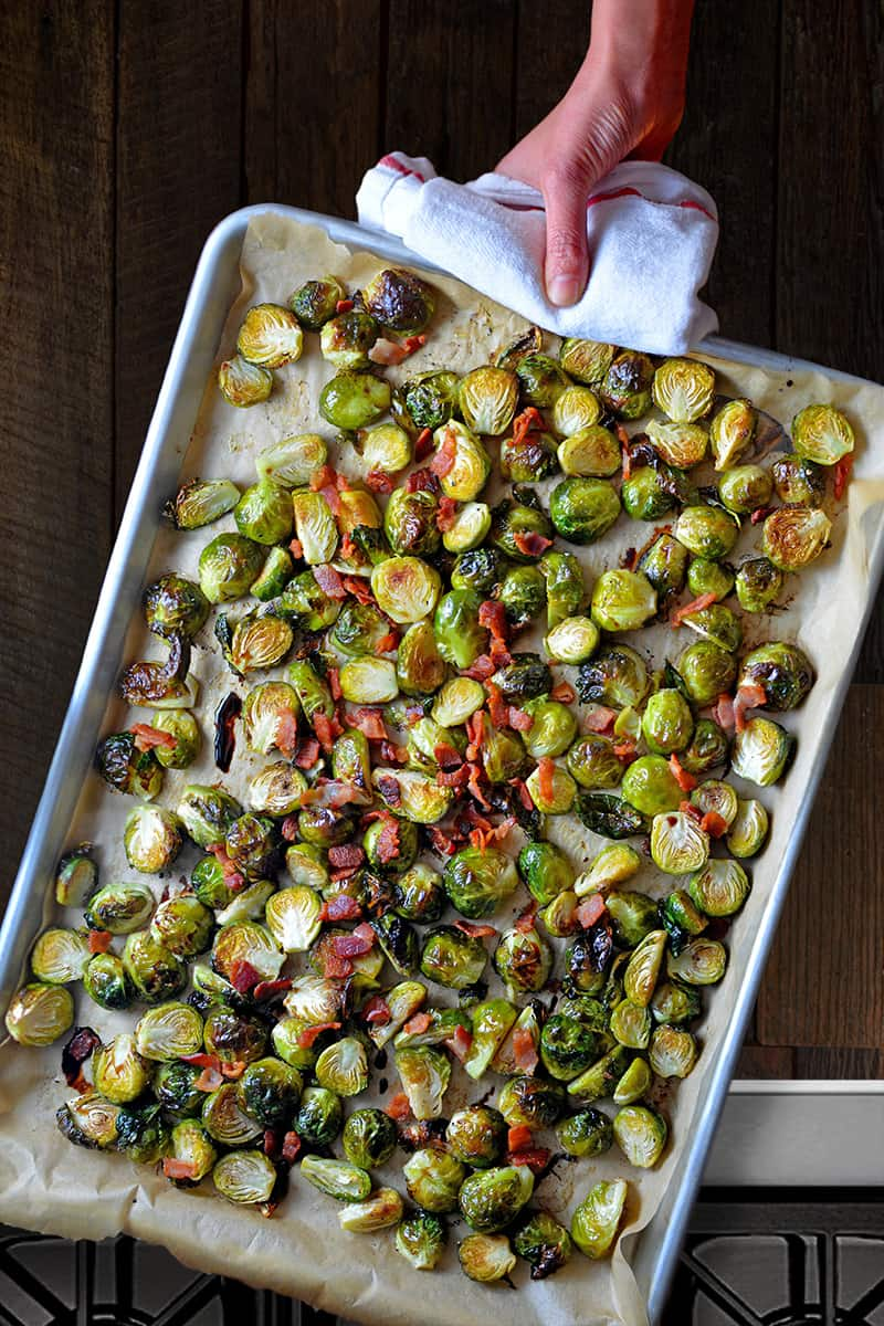 An overhead shot of a rimmed baking sheet filled with Roasted Brussels sprouts and bacon bits.