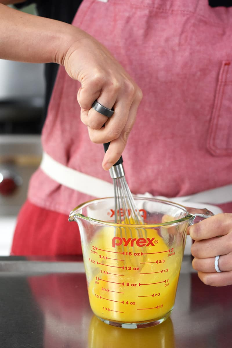 A person in a red apron is whisking eggs and salt in a 2-cup Pyrex glass measuring cup.