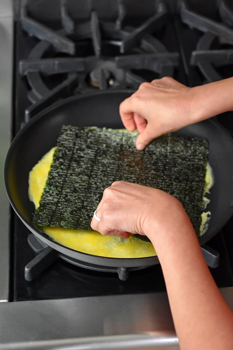 Two hands placing a rectangular piece of roasted seaweed on a thin layer of cooked egg in a non-stick skillet.