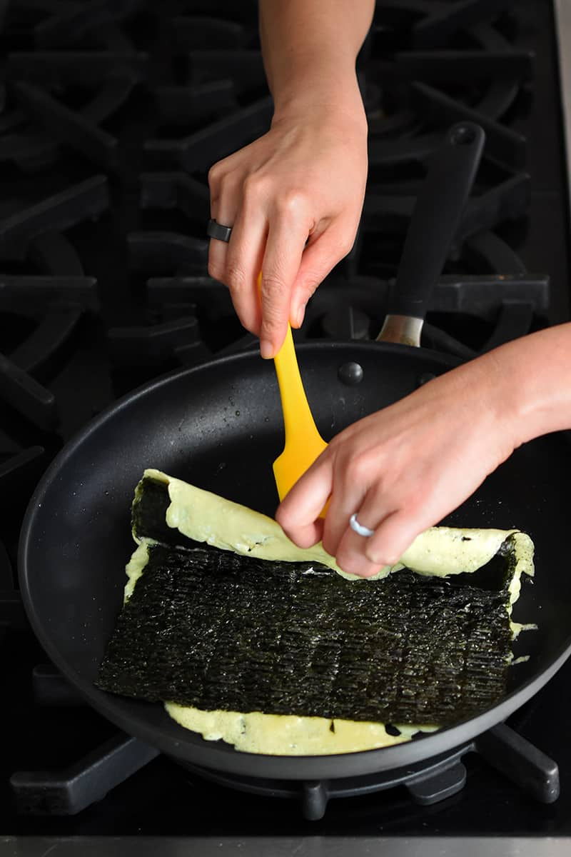 Two hands are using a yellow silicone spatula to fold over the edge of an egg omelet topped with seaweed.