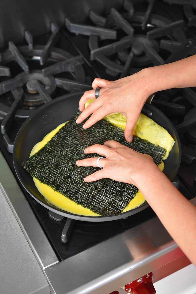 Two hands are placing a rectangular roasted seaweed in a skillet filled with a thin egg omelet.