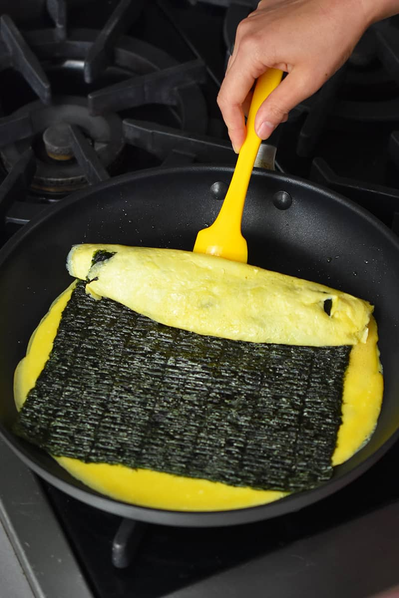 A hand is using a yellow silicone spatula to start flipping a Korean egg roll.