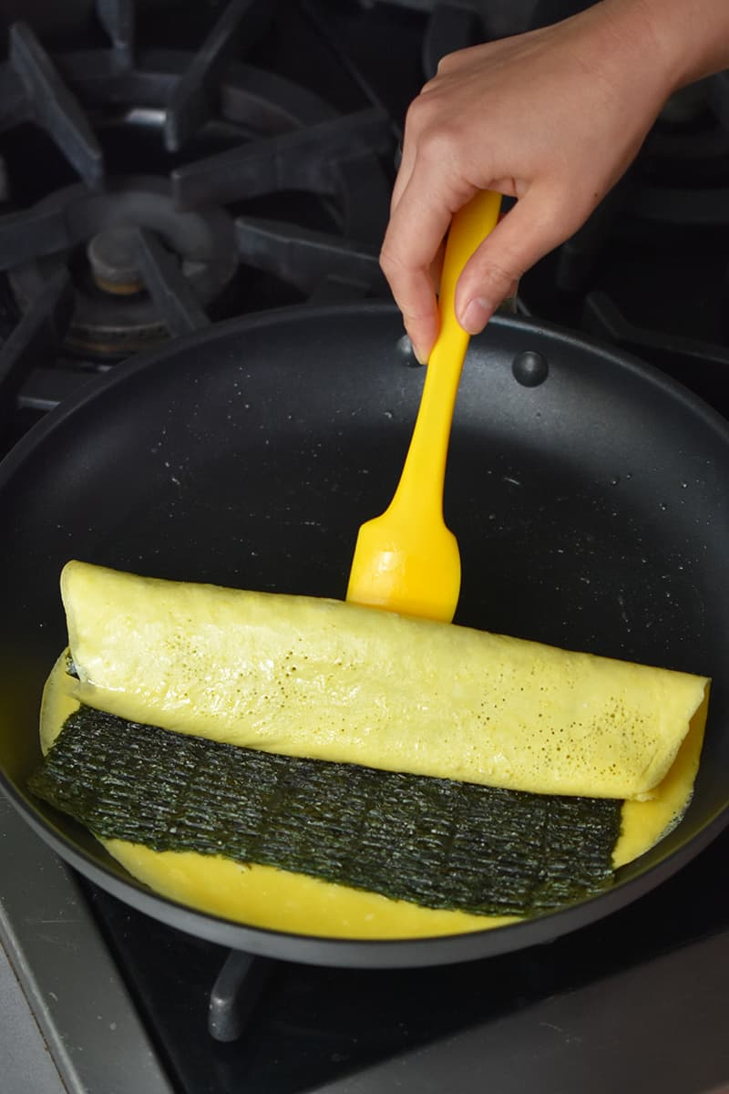 A Korean egg roll with seaweed is being rolled in a large skillet with a yellow silicone spatula.