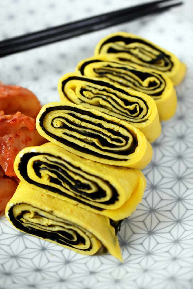A closeup shot of a cut up Korean Egg Roll Omelet with Roasted Seaweed on a white plate with gray flowers. You can see the spirals of egg and bright yellow egg in the cut-up pieces.