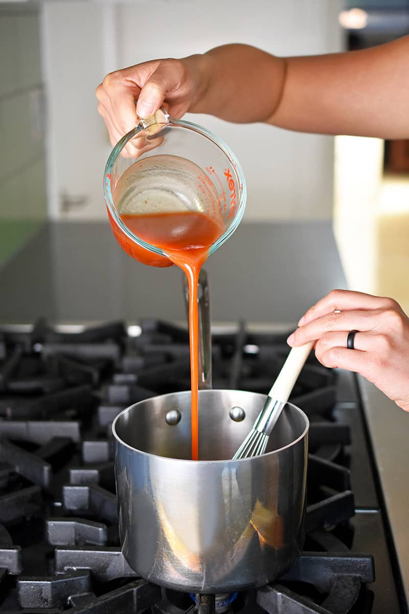 A hand is pouring cayenne pepper sauce from a liquid measuring cup into a small saucepan to make the buffalo cauliflower sauce