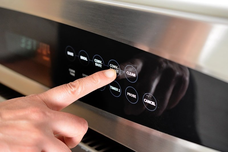 A finger pressing the convection roast button on an oven display.