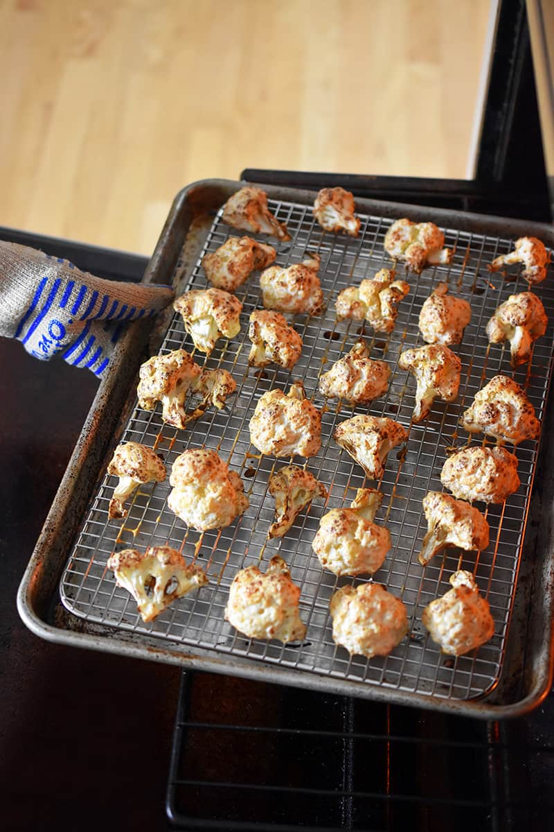 A gloved hand is removing a tray of golden brown Baked Buffalo Cauliflower from the oven.