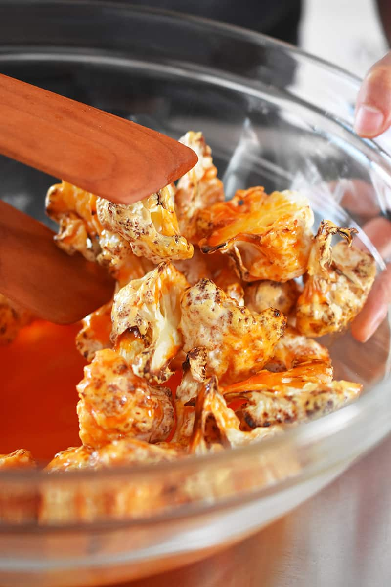 Tossing crispy cauliflower florets with buffalo sauce in a clear glass bowl.