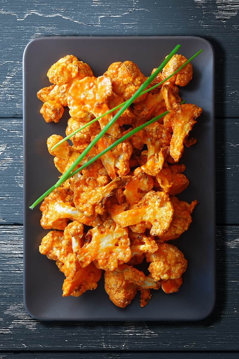 An overhead shot of baked buffalo cauliflower on a rectangular gray plate. There are three chives on top.