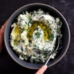 A hand is scooping paleo cauliflower colcannon from a gray bowl. The colcannon is white pureed cauliflower with flecks of green kale and scallions in it. There is melted ghee on top.