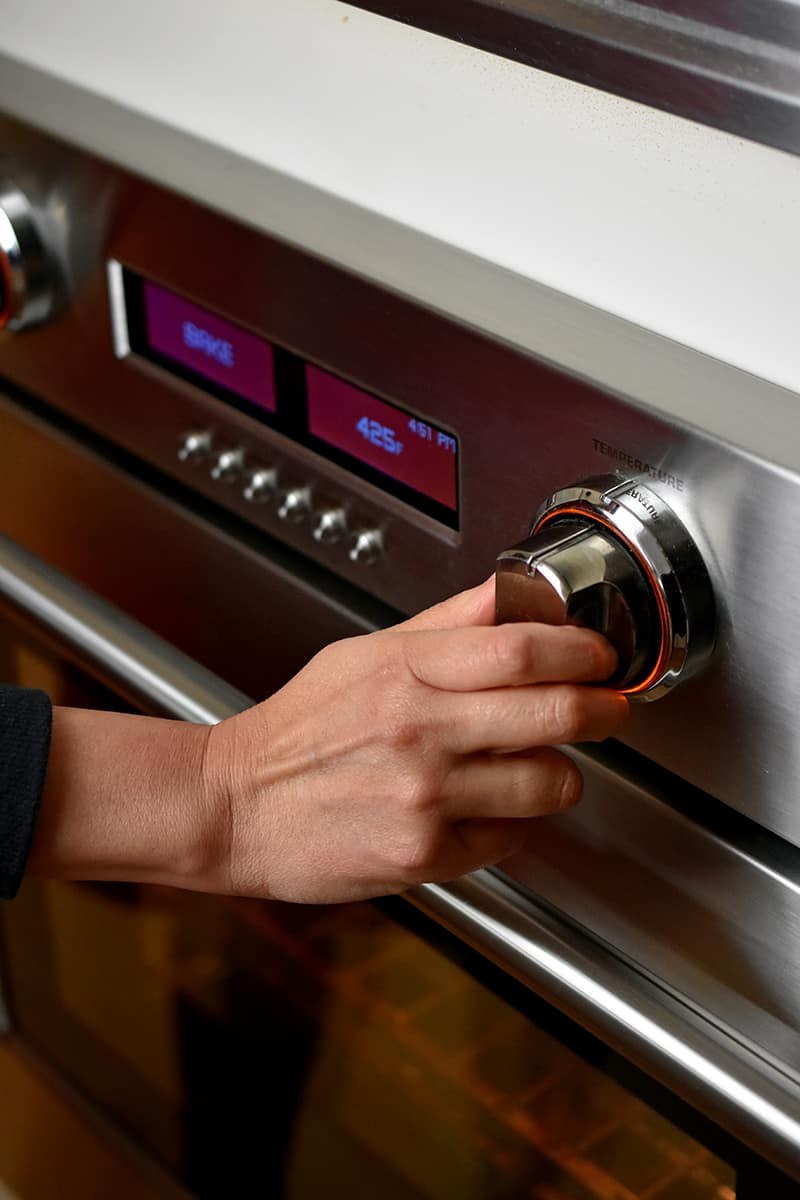 A hand is turning the dial on a wall oven to preheat it.