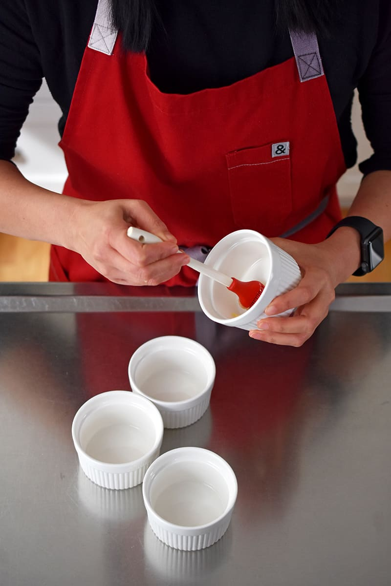 A person in a red apron is brushing melted ghee into a white ramekin. There are three other ramekins in front of her.