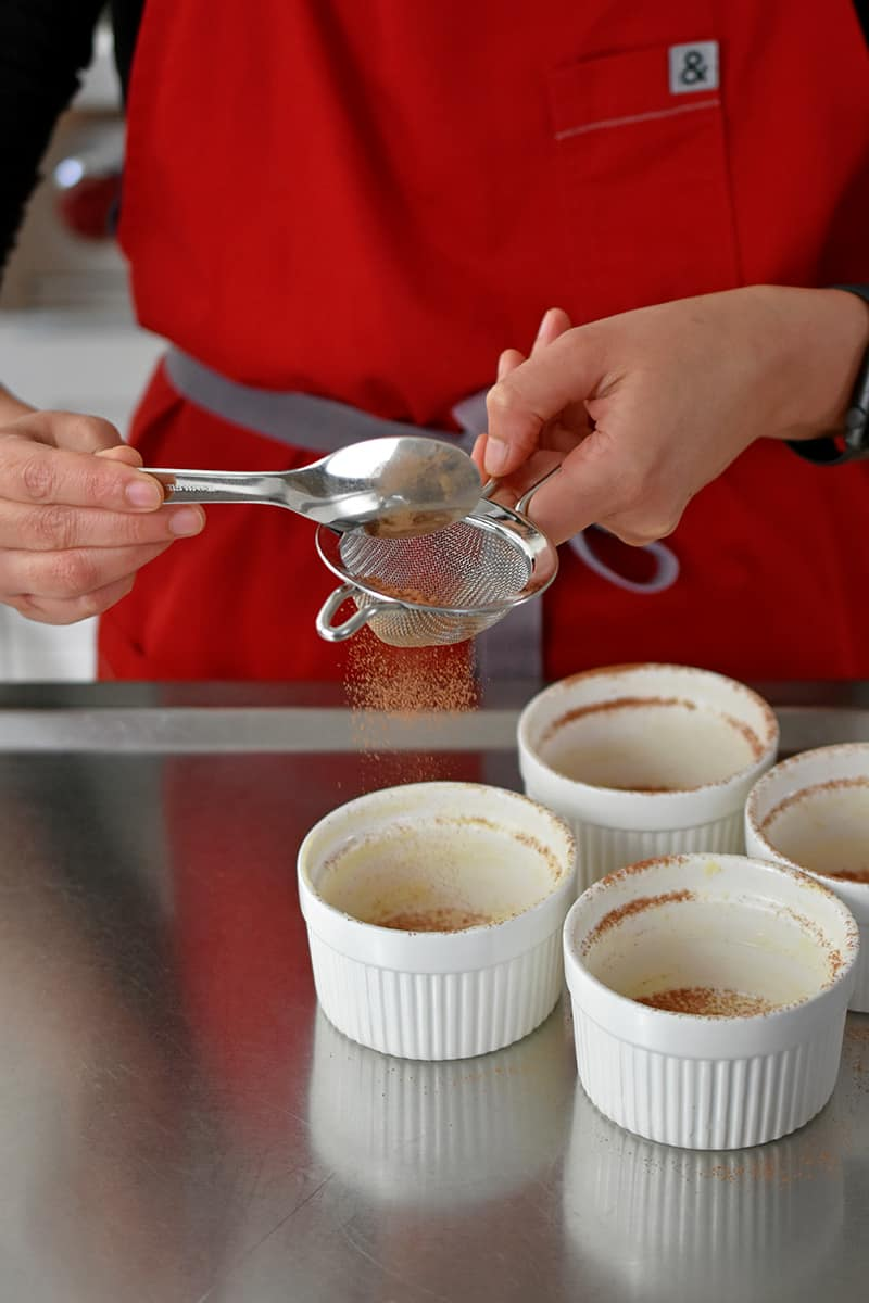 A person in a red apron is tapping unsweetened cocoa powder from a small mesh sieve into a greased small white ramekin.