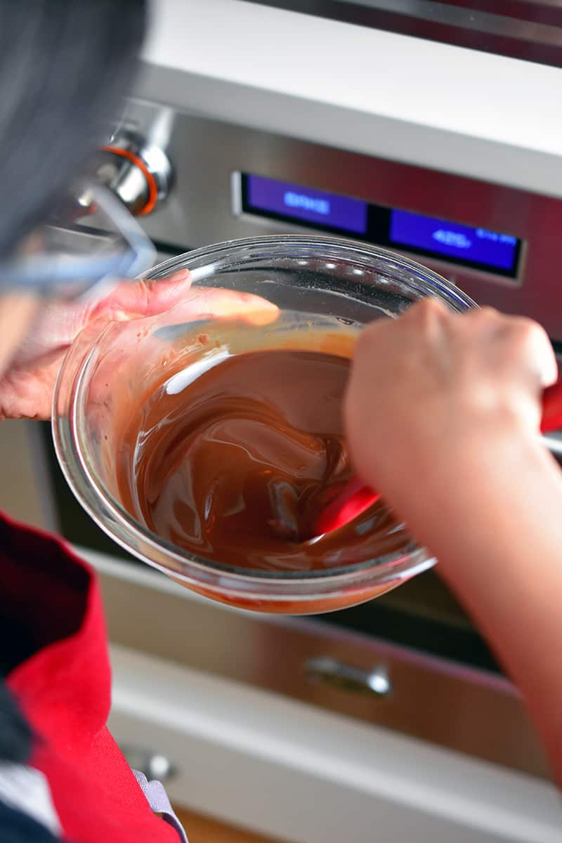 Someone stirring melted chocolate in a glass bowl with a red silicone spatula.