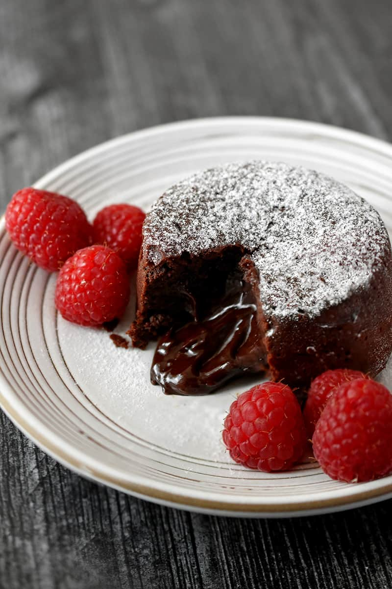 A closeup shot of a white plate with a chocolate lava cake opened to show the gooey center. There is powdered keto confectioners sugar on top and raspberries on the side.