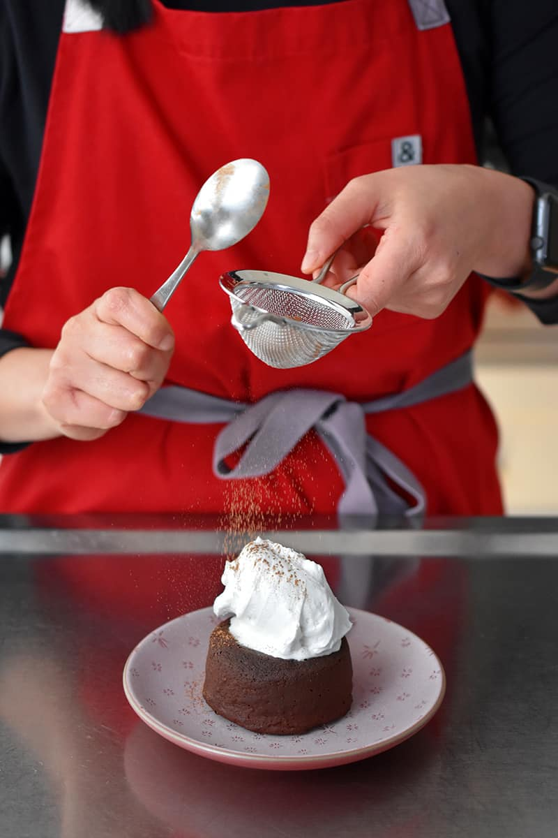 A person in a red apron tapping cocoa powder on top of a lava cake with whipped coconut cream on top.