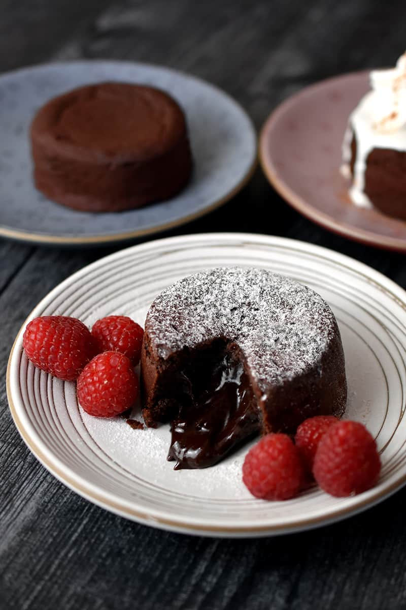 Three plates of paleo chocolate lava cake: the one in front is topped with powdered sugar and next to raspberries, the one in the back is unadorned, and the one in the back on the right has melted whipped coconut cream on top.