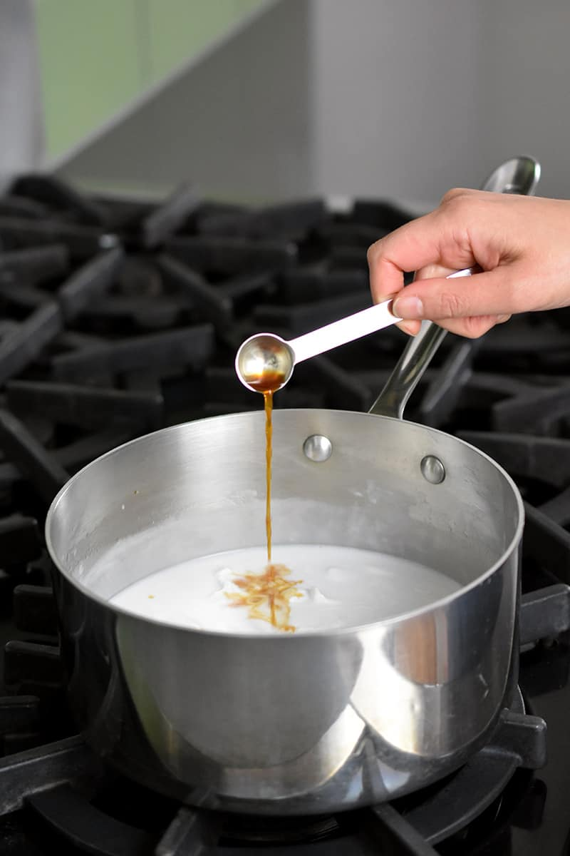 A hand is adding vanilla extract from a measuring spoon into a saucepan filled with coconut milk.