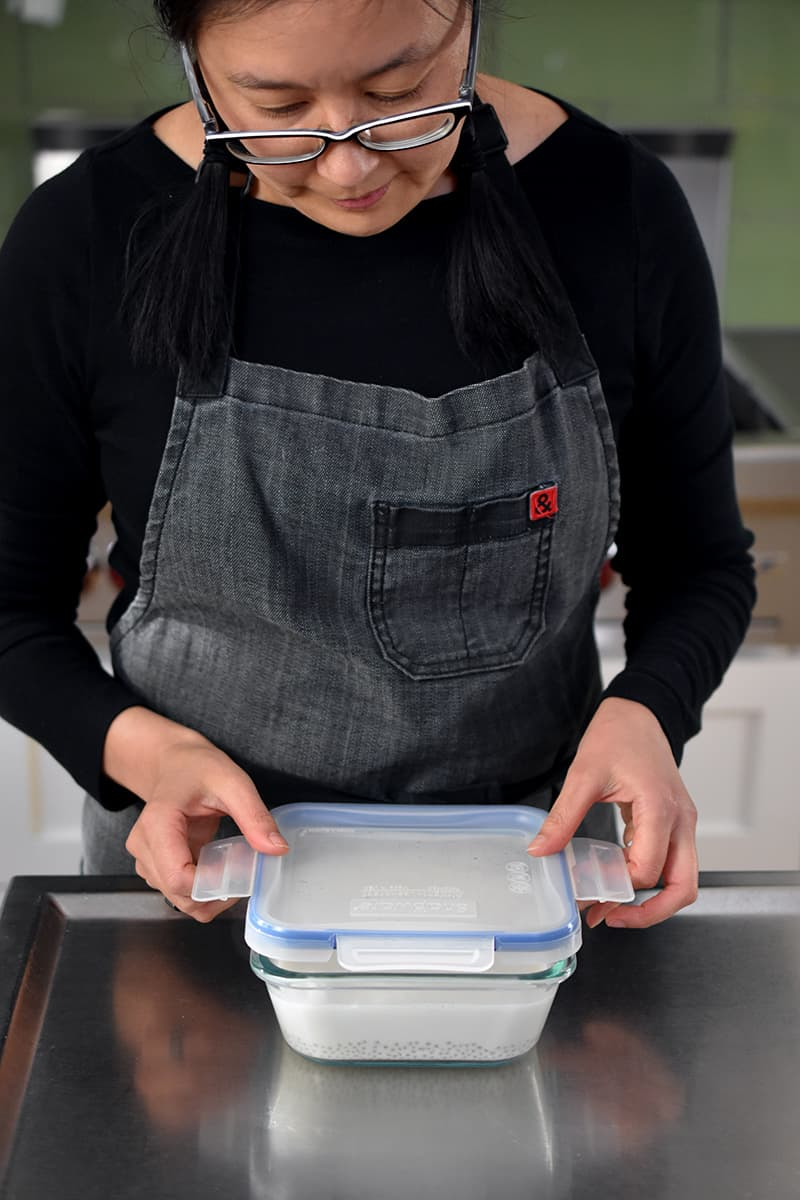 A woman in a gray apron is putting a lid on a square glass container filled with coconut sago.