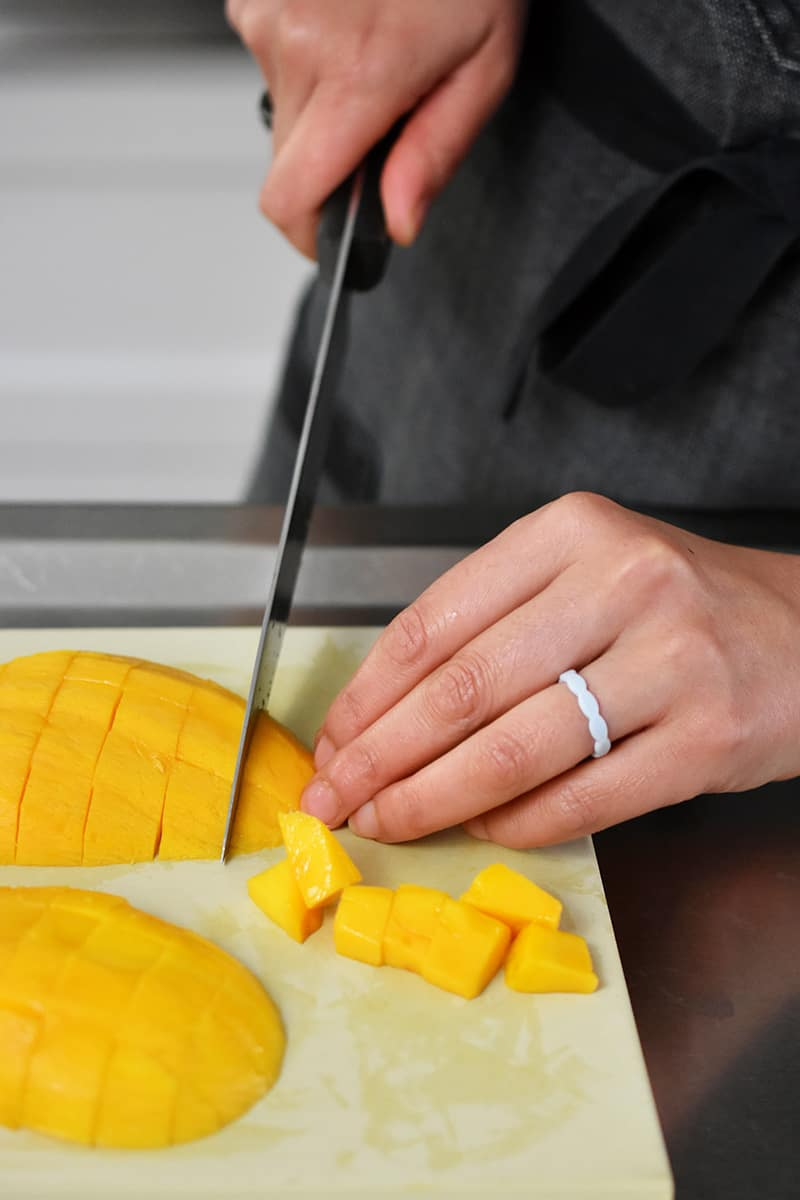 A closeup of someone cutting peeled mango into cubes on a rubber cutting board.