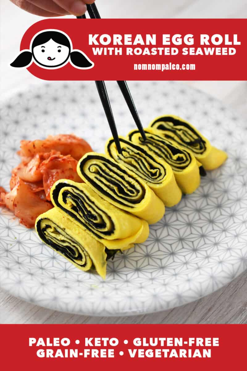 A white plate with a gray flower pattern is topped with a Korean rolled egg omelet with seaweed. There is a small pile of kimchi on the side and a pair of chopsticks is lifting up a piece. The red banner at the bottom says paleo, keto, vegetarian, and gluten-free.