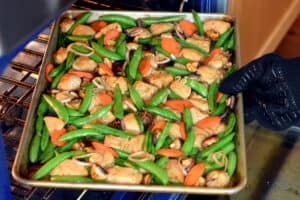 A side view of a gloved hand removing a sheet pan chicken stir fry dinner out of the oven to serve.