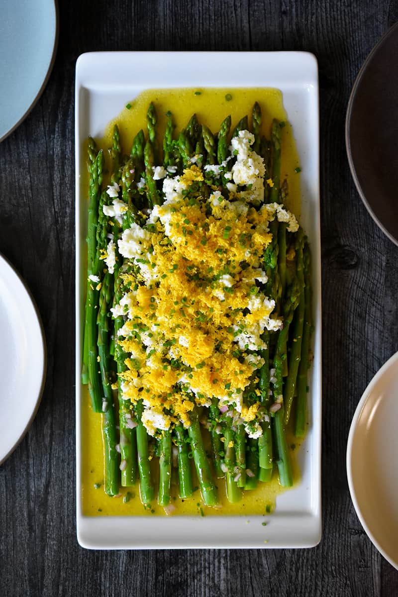 An overhead shot of a rectangular plate filled with Asparagus Mimosa, cooked asparagus tossed with a lemon vinaigrette and topped with chopped hard boiled eggs and chives.