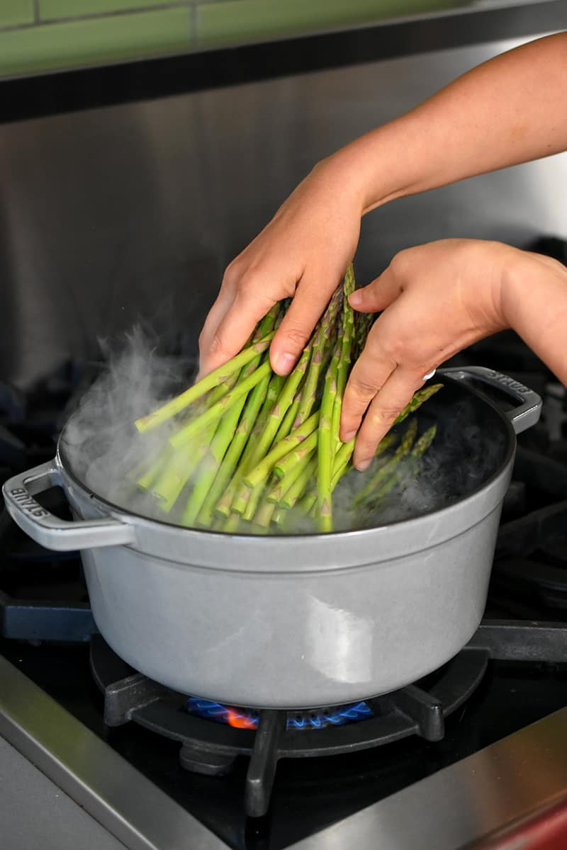Two hands adding asparagus to a gray stock pot filled with boiling water.