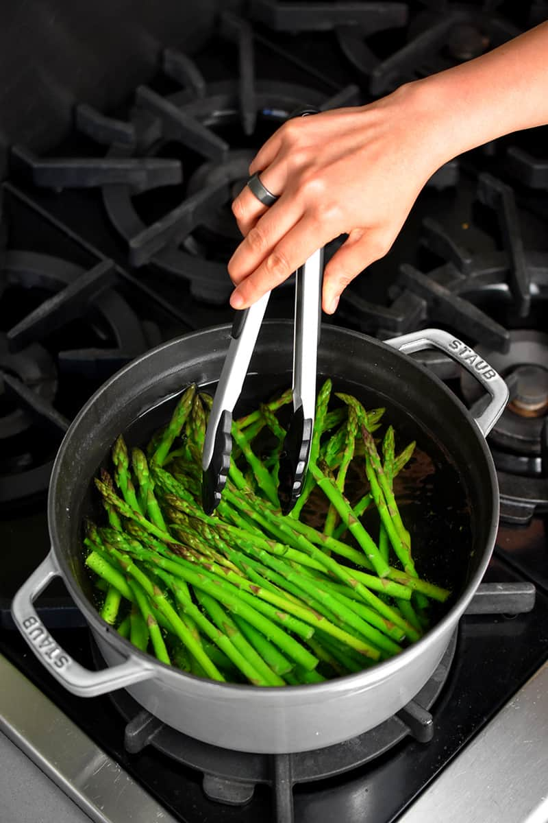 An overhead shot of a gray pot filled with boiling water and bright green asparagus. A hand with a pair of tongs is mixing them around.