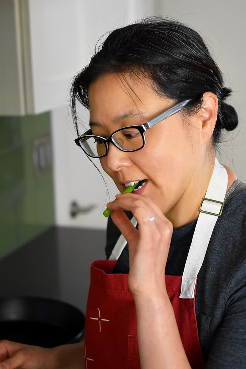 An Asian woman in a red apron is biting on a piece of asparagus.