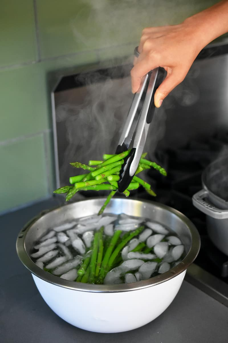 Someone using tongs to place cooked asparagus into a large bowl of ice water.