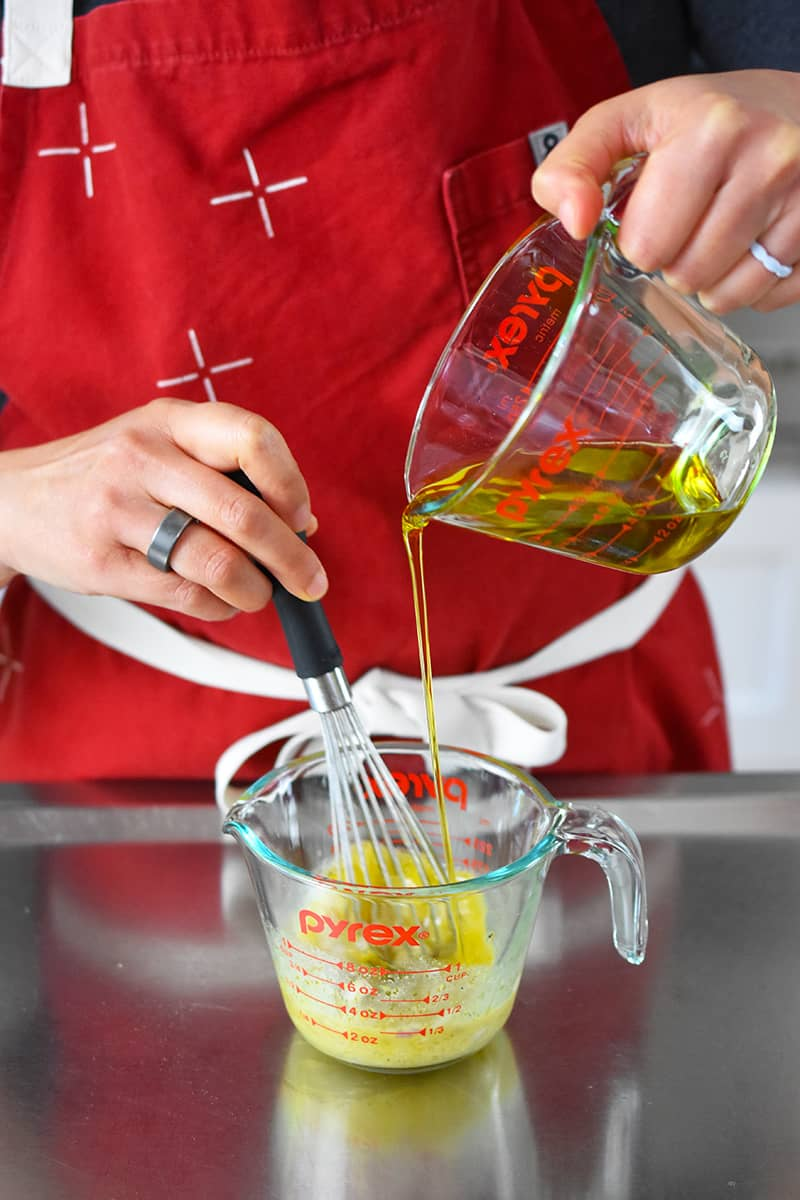 Someone in a red apron is whisking extra virgin olive oil into a measuring cup with vinaigrette ingredients.