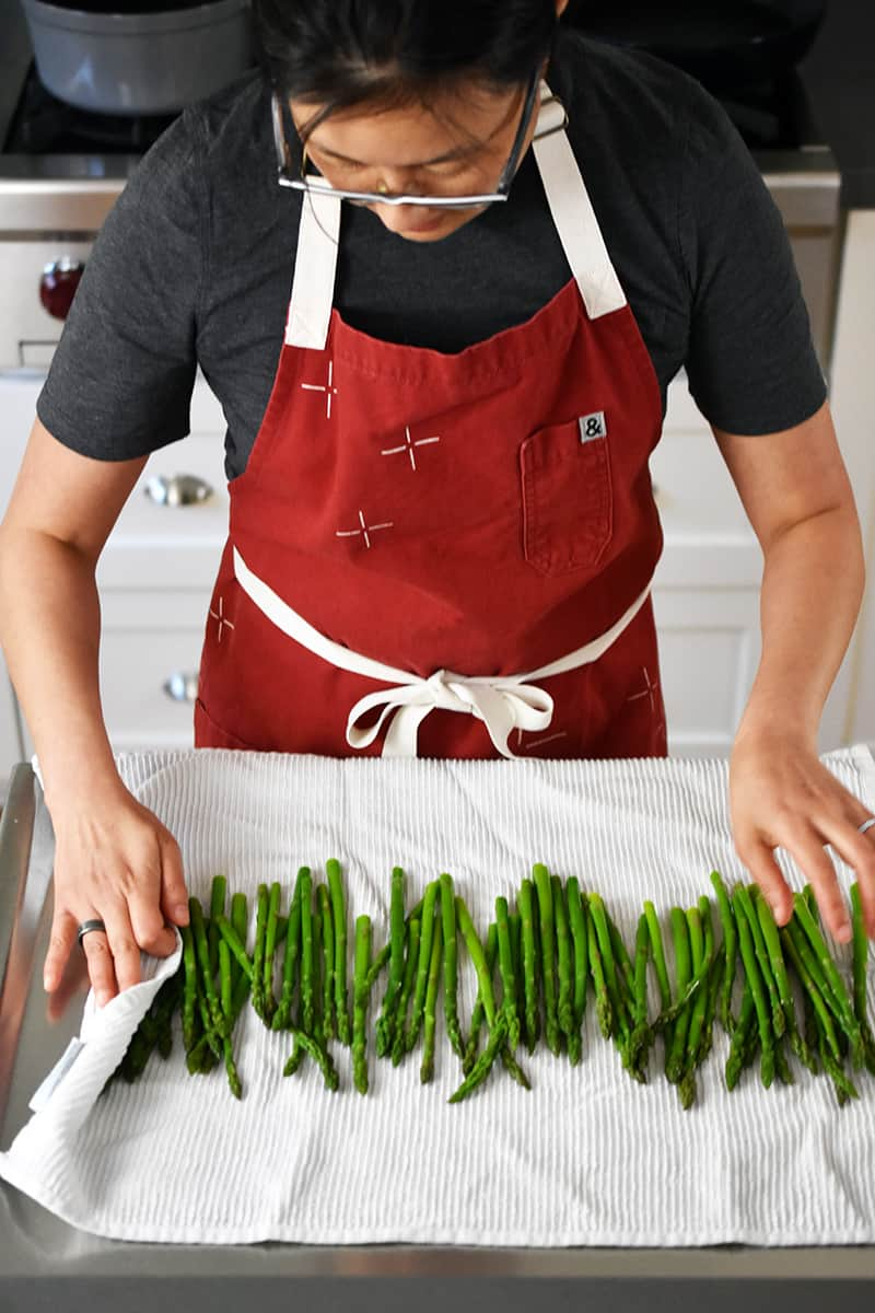 Someone in a red apron has cooked asparagus on a large white kitchen towel.