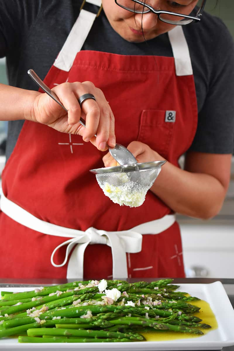 A woman in a red apron is pressing egg whites through a small sieve on top of cooked asparagus