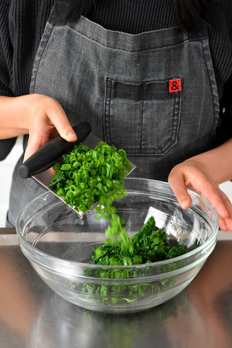 A person in a gray apron is transferring chopped kale and scallions with a bench scraper into a large glass bowl.