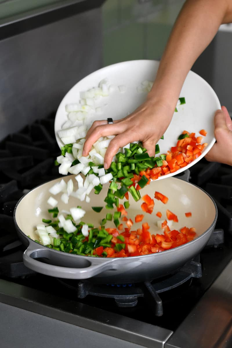 A hand is pushing diced onions, red bell peppers, and poblano peppers from a white plate into a gray enameled cast iron Le Creuset braiser.