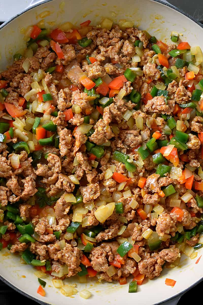 Overhead shot of a pan filled with cooked Mexican chorizo, diced bell peppers, and onions.