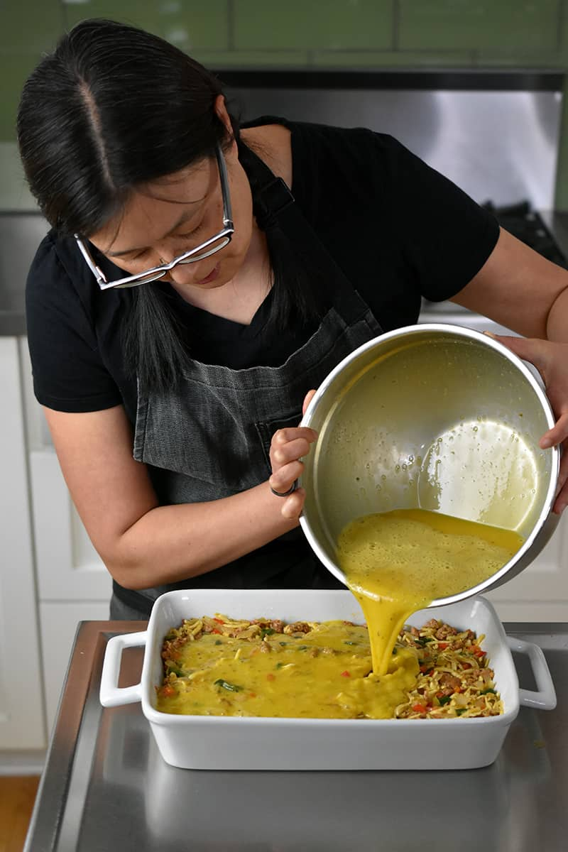 An Asian woman in glasses is pouring a big bowl of whisked eggs into a casserole pan to make Mexican Breakfast Casserole.