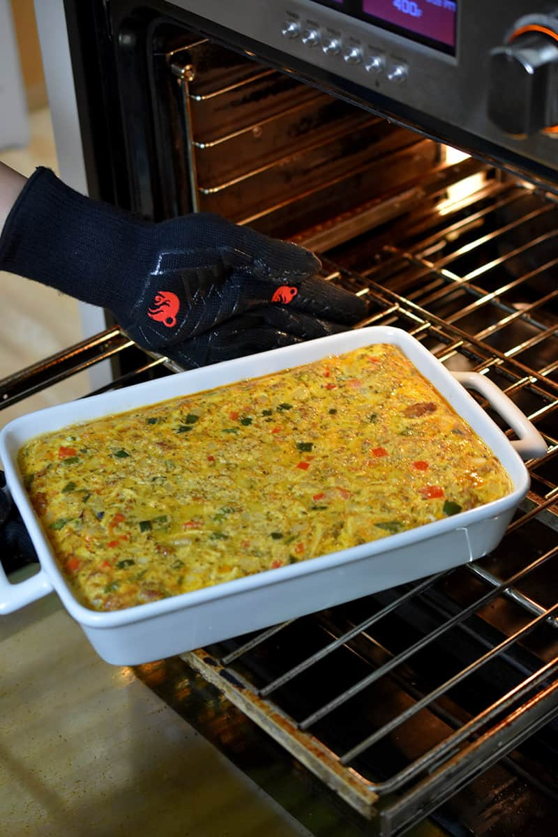 Rotating a white casserole filled with Mexican Breakfast casserole at the midway point during baking.