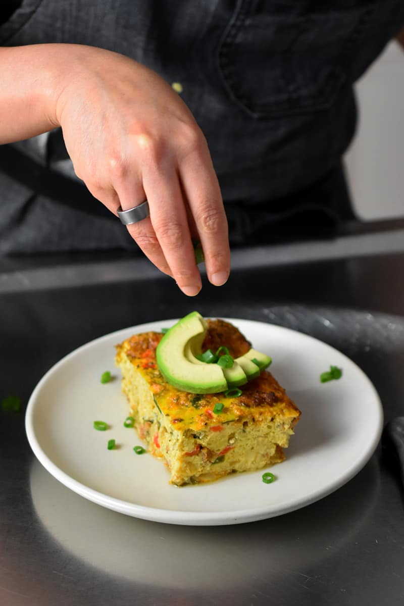 A hand is sprinkling sliced scallions on a slice of Mexican breakfast casserole with avocado slices on top