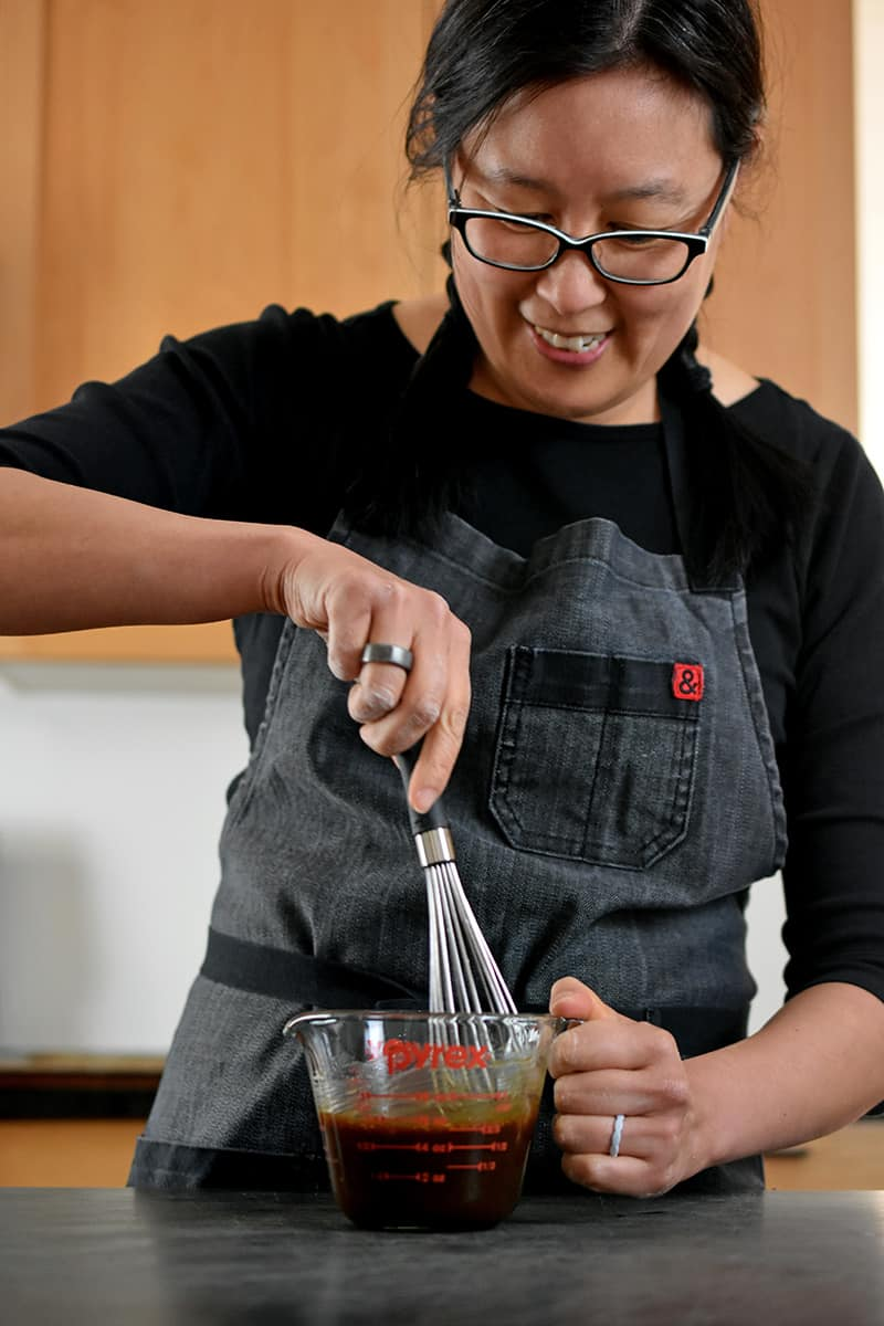 A smiling Asian woman is whisking All-Purpose Stir-Fry Sauce with other seasonings in a 2 cup Pyrex measuring cup