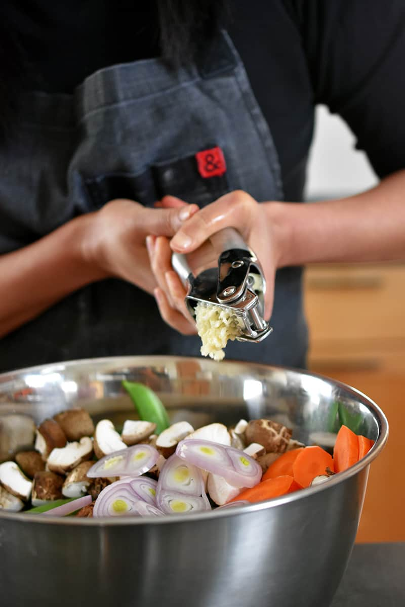 Someone in a gray apron is squeezing a garlic press with two hands and adding the minced garlic to a big silver bowl filled with chopped vegetables