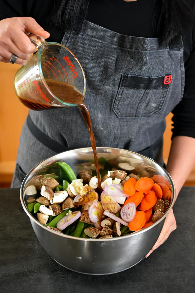 A person in a gray apron is pouring a brown sauce into a large metal bowl filled with chopped carrots, sugar snap peas, shallots, shiitake mushrooms, and minced garlic.