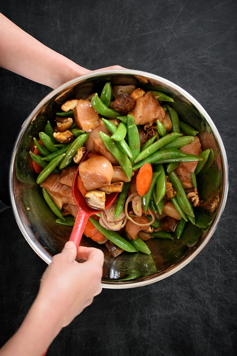 An overhead shot of someone mixing vegetables and chicken with stir-fry sauce