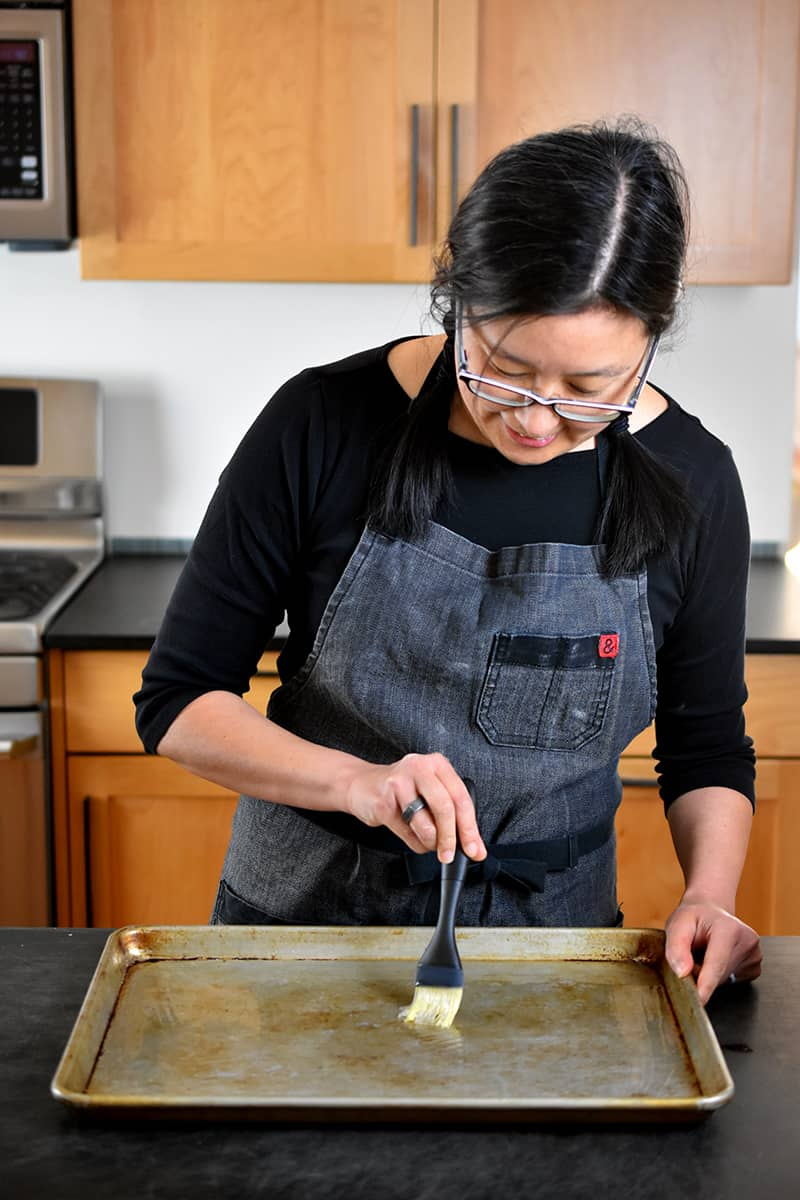 A brunette Asian woman is brushing avocado oil on a rimmed baking sheet.