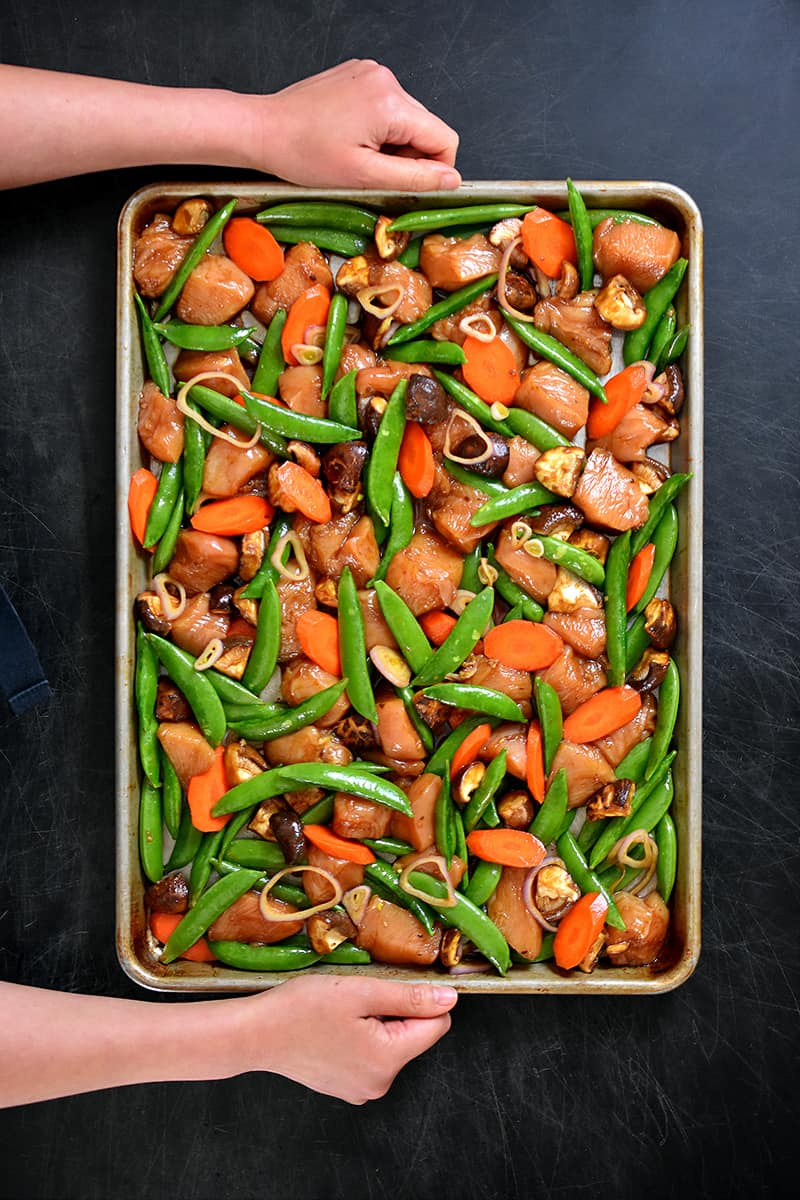 An overhead shot of a sheet pan filled with uncooked stir-fry chicken and vegetables in a single layer.
