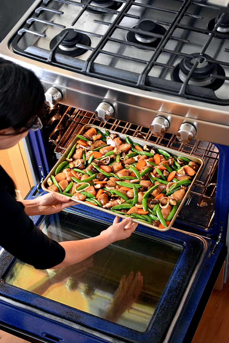 An Asian woman is bending down to place a sheet pan filled with chicken and vegetables into an open oven.