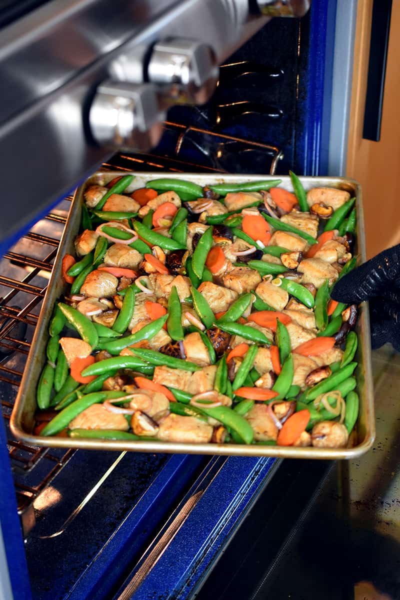 A gloved hand is rotating a sheet pan chicken and vegetable dinner at the midway point while it is baking.