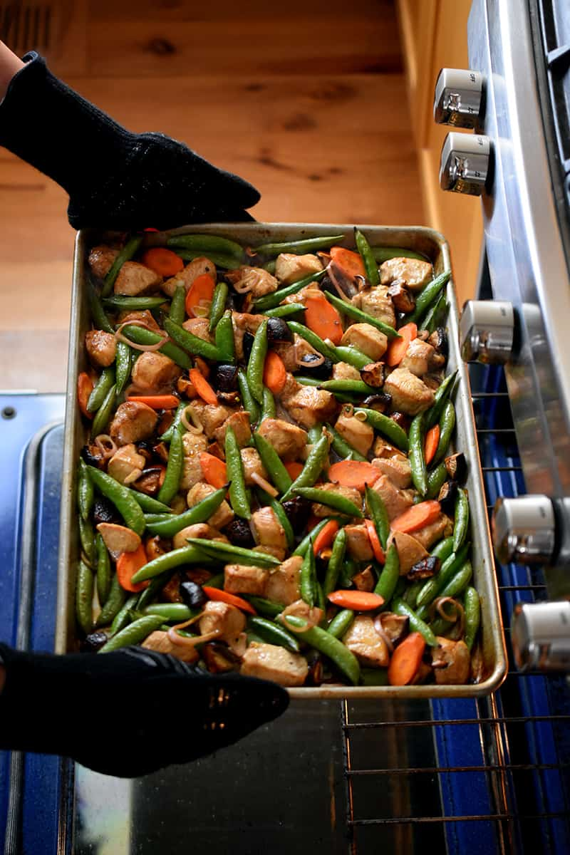 Two gloved hands are removing a sheet pan chicken stir-fry from an open oven,